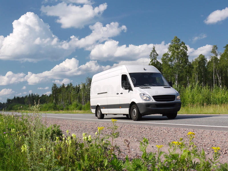 White van on summer rural highway. White van on summer highway Scandinavia, landscape royalty free stock photo