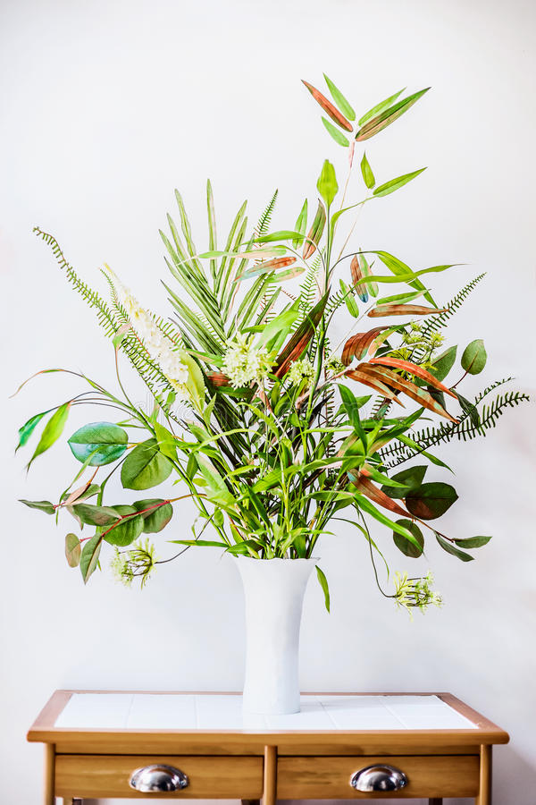 White vase with bunch of various green plant on table. Florist arrangements with variety of green tropical plants. Home decor with stock images