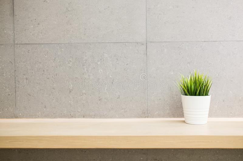 White vase green grass on the wood shelf. On granite tile wall of copy space royalty free stock image