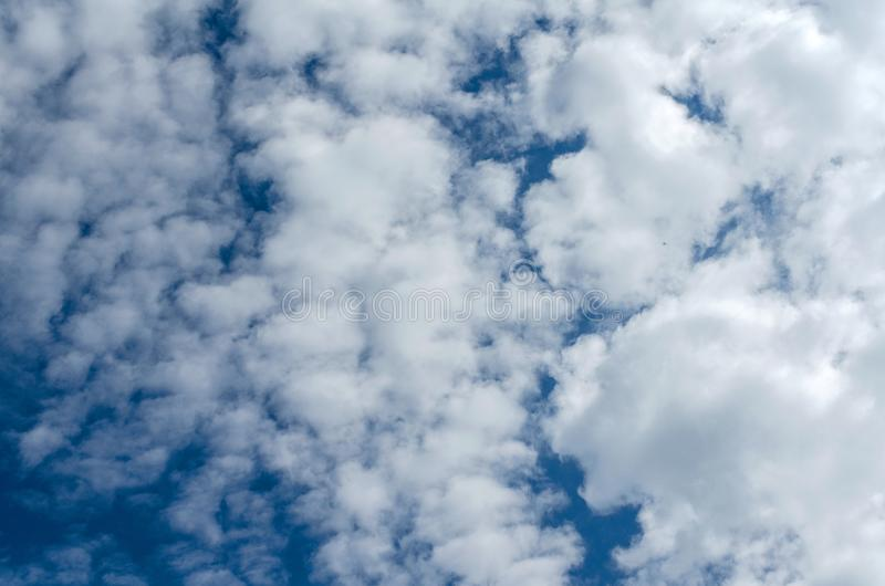 White vast fluffy clouds and blue sky on a clear day. A beautiful horizontal background. royalty free stock photo