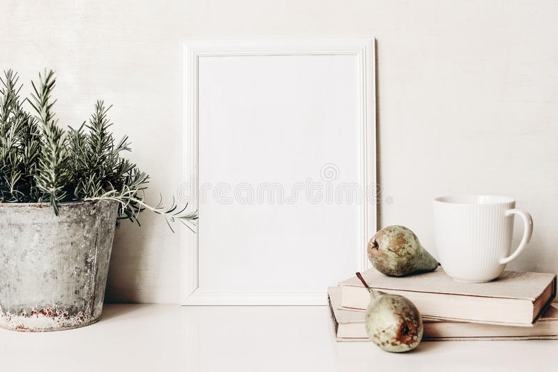 White vertical blank wooden frame mockup. Composition of rosemary herb in old metal flower pot, books, cup of coffee and royalty free stock photos
