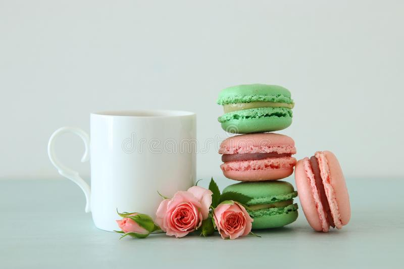 White vintage cup of coffee and colorful macaron or macaroon over pastel wooden table. royalty free stock images