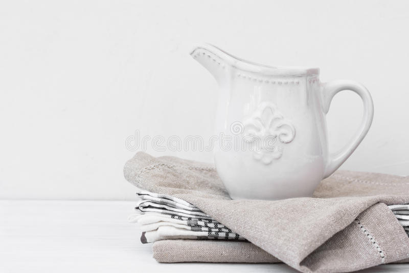 White vintage pitcher on a stack of linen towels, styled image with copyspace for product marketing royalty free stock images