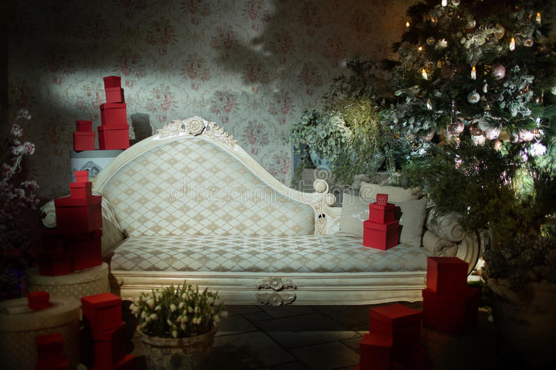 white vintage sofa for background wall with wallpaper and furnished with boxes of gifts and a Christmas tree decorated royalty free stock photo