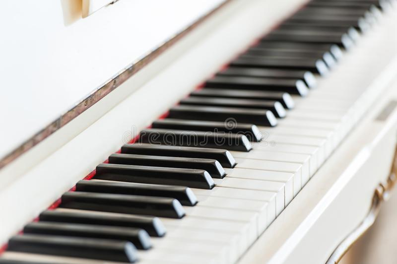 White vintage wooden piano keyboard closeup. White vintage wooden piano black and white keyboard closeup in luxury bright interior royalty free stock images