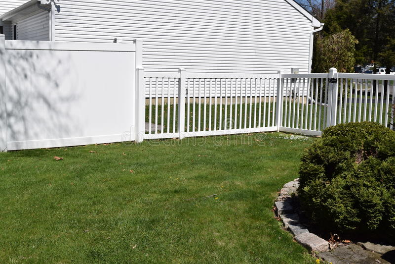 White vinyl backyard fences. Contrasting white vinyl backyard fencing stock image