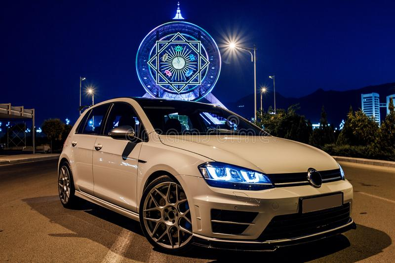 White vw golf in the evening next to the Ferris wheel.. View from the corner. Turkmenistan, October 2017: White vw golf in the evening next to the Ferris wheel royalty free stock image