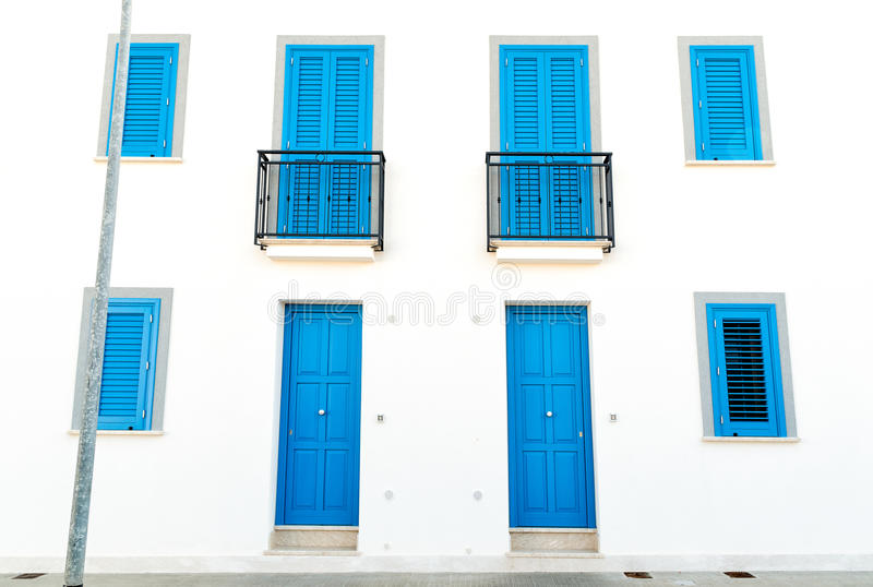 The white wall with blue doors and windows royalty free stock image