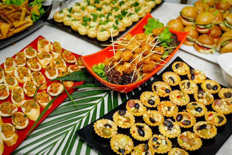 Evening buffet table with treats. Fruit tartlets, mini burgers, chicken skewers stock photo