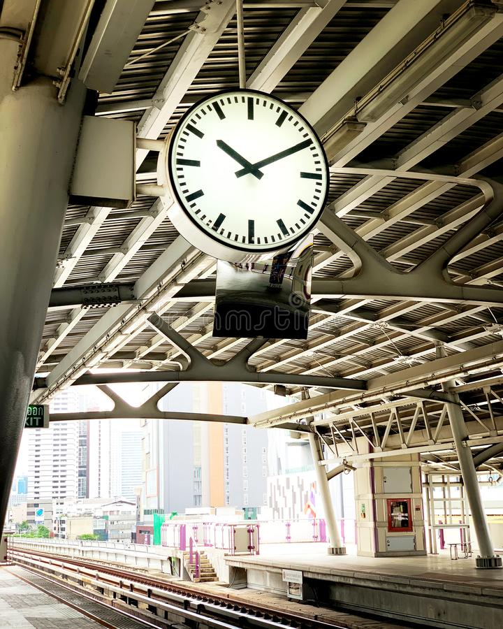 White wall clock with silver edge hanging on roof at train platform. stock images
