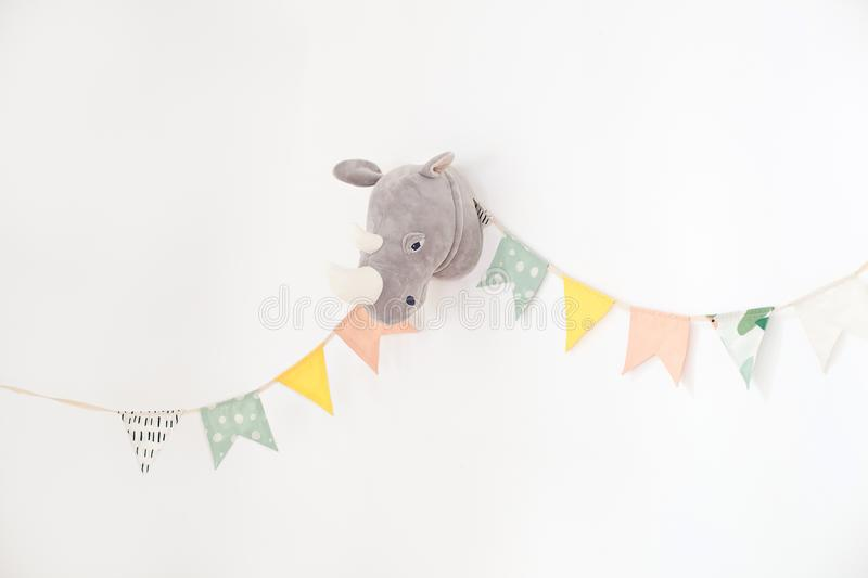 The white wall is decorated with multi-colored flags for children. Design a vintage flag with fabric over white cement wall textur. E background. Birthday decor stock photography
