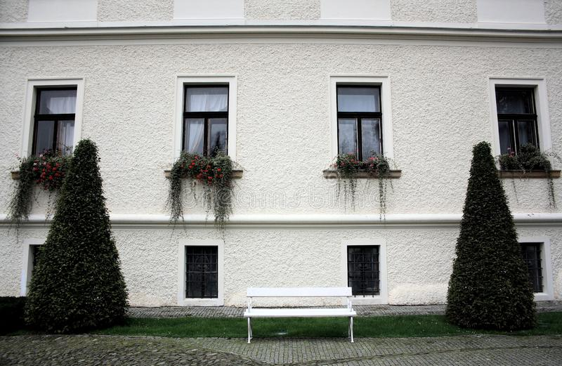 White wall with four long windows and plants, two conus-shaped bushes and a white bench stock photography