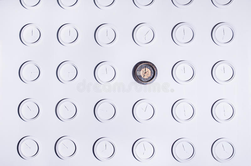 White wall with identical round white not numeral clocks and one unique dark clock. Time concept background stock images