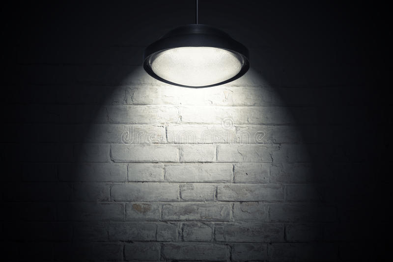 White wall illuminated with spot light. White brick wall illuminated with spot light from the ceiling lamp. Dark interior as background with copy space stock image