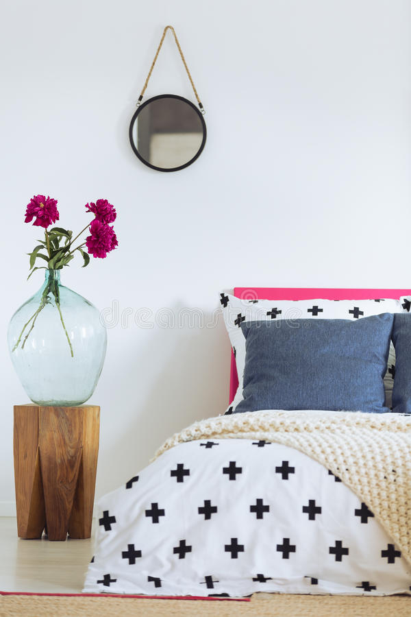 White wall and patterned bedclothes. White wall, round mirror, glass vase and patterned bedclothes stock photos