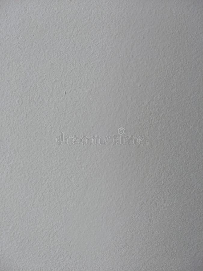 White wall texture with a side lighting. White painted wall texture. With a smooth lighting from the left side of the frame, adding contrast to the texture stock photo