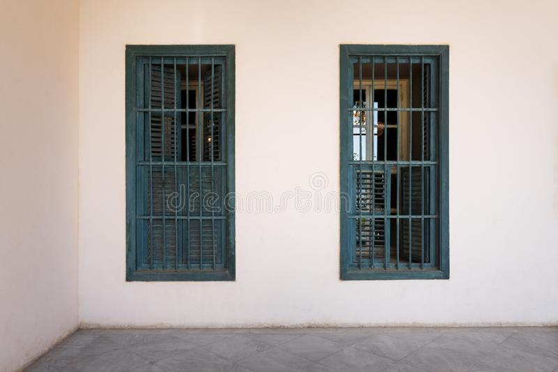 White wall with grunge windows with wooden green shutters and wrought iron bars and marble floor stock images