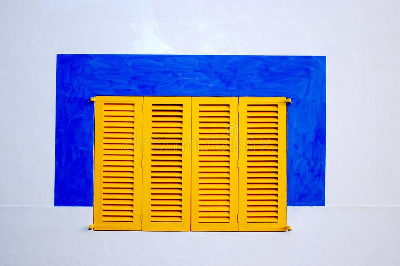 A white wall with yellow window blinds and a blue painted square around it royalty free stock photography
