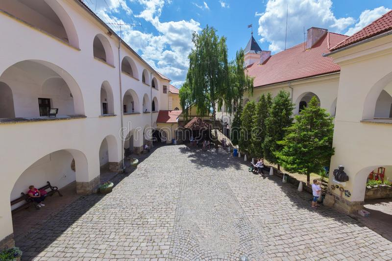 White walls with arches of the courtyard of the Mukacheve castle. Tourists examine the well royalty free stock image