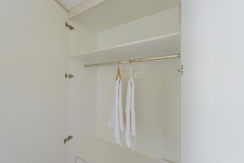 White wardrobe closet. With Hangers, bath robes For guests staying in hotel royalty free stock photos