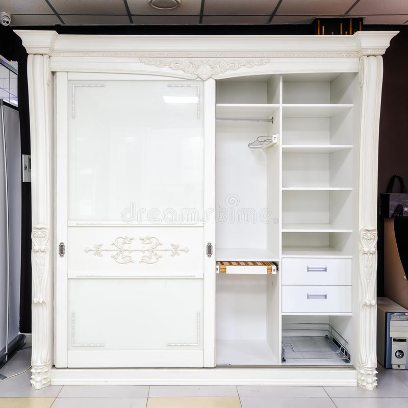 White wardrobe with sliding doors, drawer and shelves, vintage style.  royalty free stock image