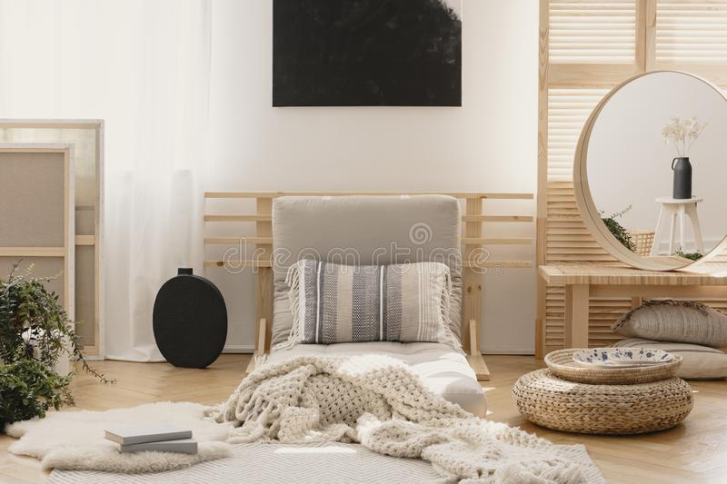 White warm blanket and patterned pillow on beige futon in stylish natural bedroom interior with elegant round mirror in wooden stock images