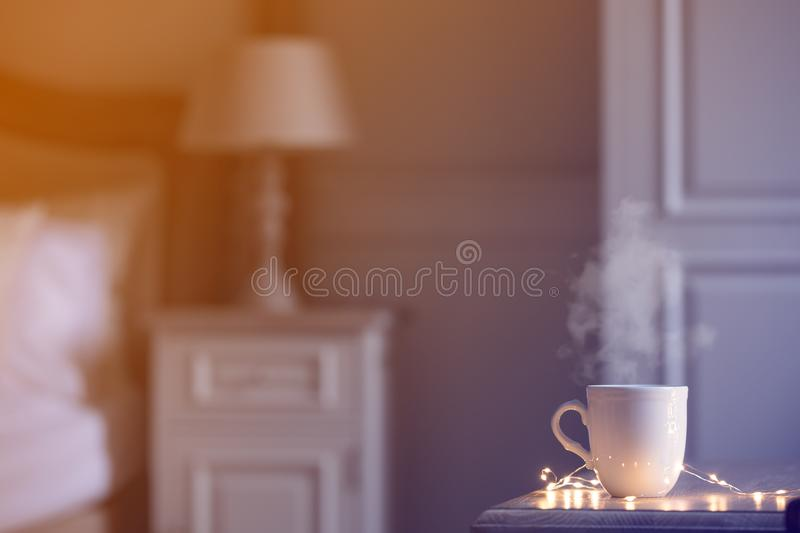 White warm cup of tea of coffee standing on wooden table. In bedroom stock photography
