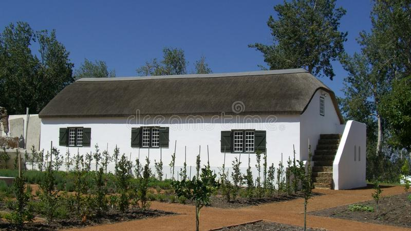 A white wash country cottage with reed roof royalty free stock photo