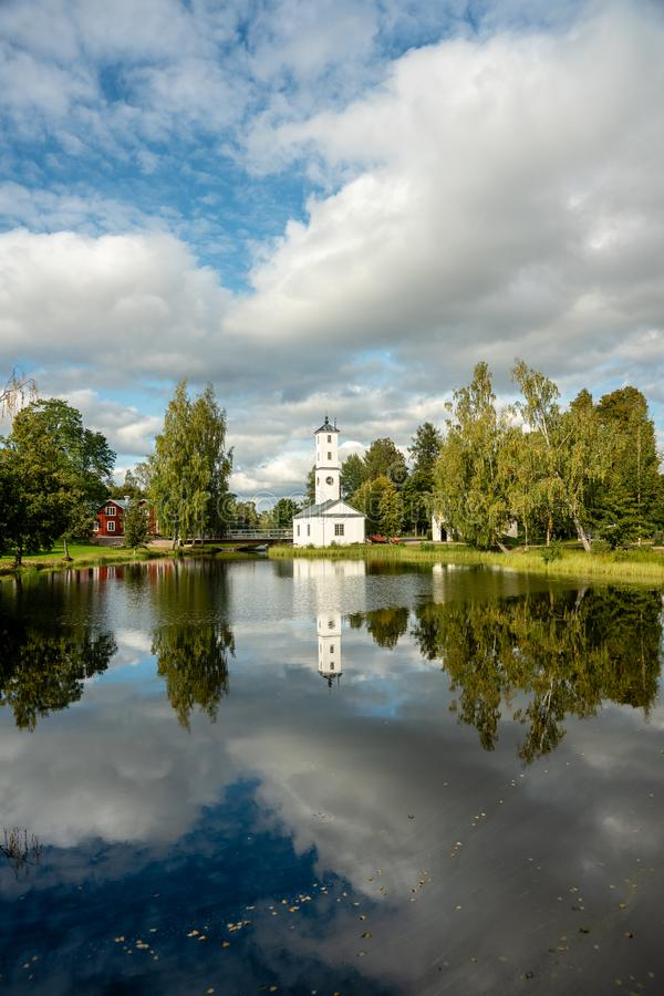 White watch tower building in summer sunshine. Beautiful tall tower building in Stjärnsund, Sweden. In bright summer sunshine mirroring in the water in front royalty free stock photo