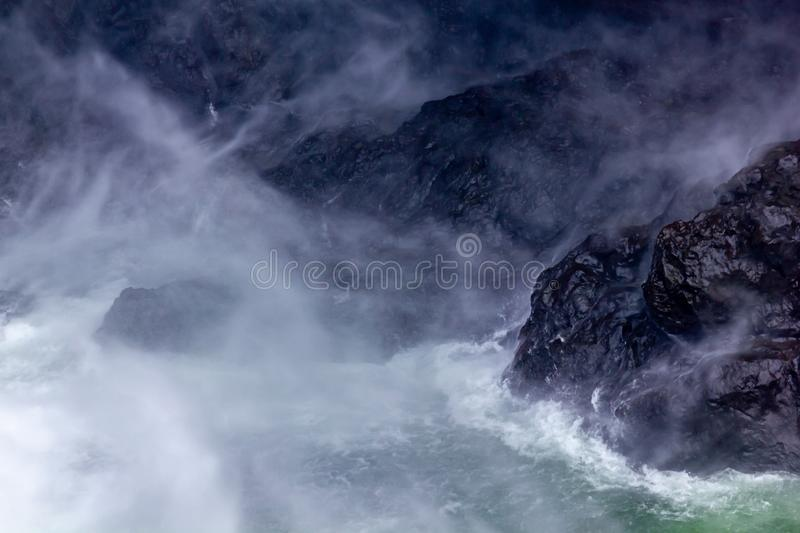 white water and dark rock create abstract mist pattern stock photo