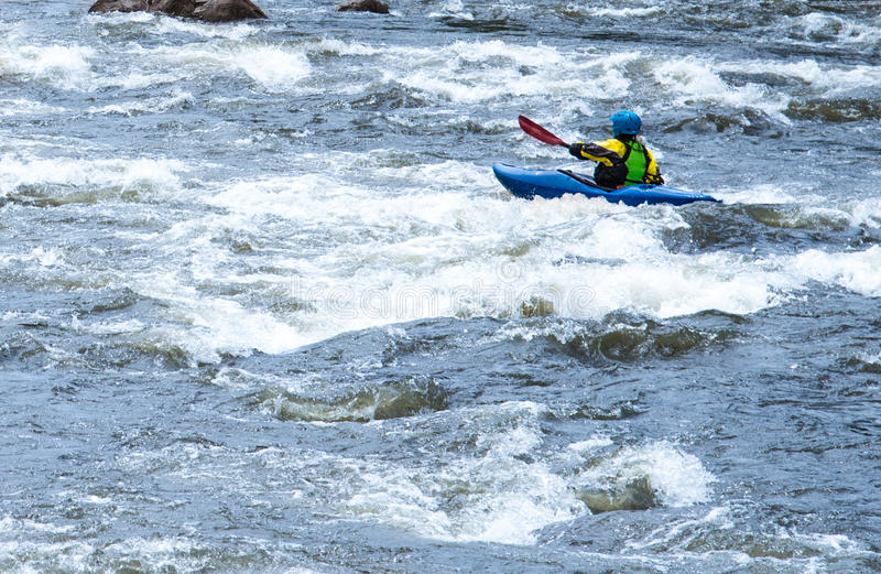 White Water Rapids Kayaking. Man or Woman in kayak floating through white water rapids on a river in Colorado. Kayaking is a healthy and popular recreational stock image