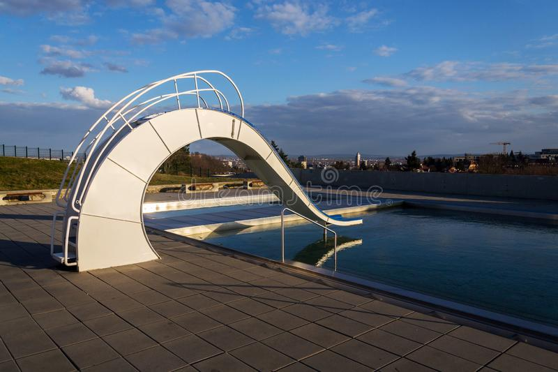 White water slide with outdoors pool, beautiful sunset, clear blue sky. Background stock images