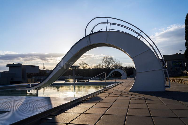White water slide with outdoors pool, beautiful sunset, clear blue sky. Background stock image