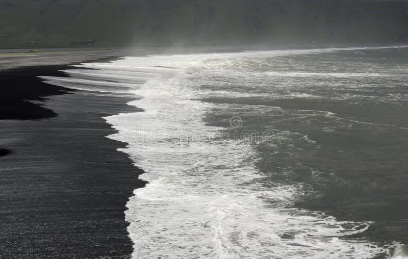 White waves on black beach royalty free stock photos