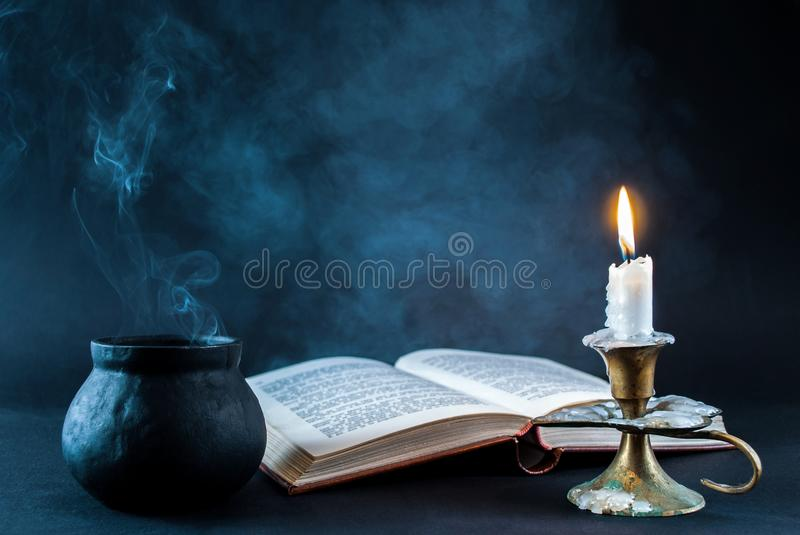 Candle in candlestick burning and smoky pot and old open book on dark and smoked background stock images