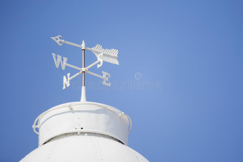 White weather vane on the roof stock images