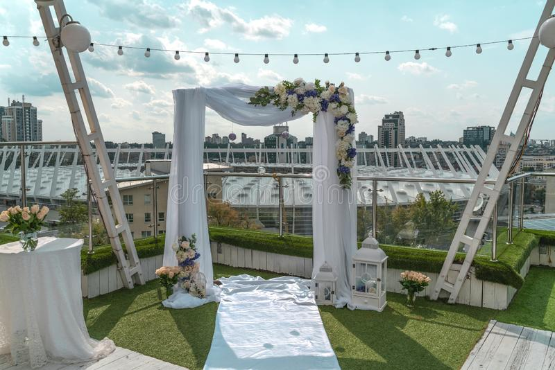 White wedding arch with flowers on building roof in megapolis center under the open sky on sunny day in summer, Kiev, Ukraine. royalty free stock photography