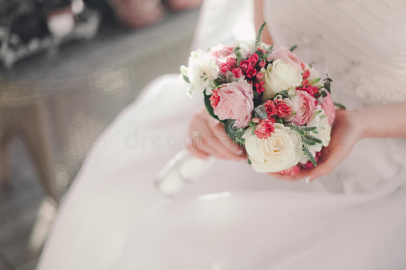 White wedding bouqet and hands of a bride.  stock photos