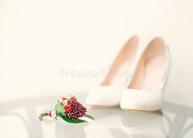 White wedding bride`s shoes and groom`s bouquet in the foregroun. White wedding bride`s shoes and groom`s small bouquet in the foreground. Wedding day stock photo