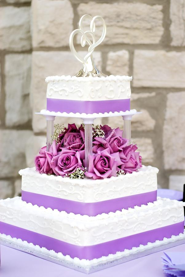 White Wedding Cake. Classic 3 tier white wedding cake with purple flowers and ribbon royalty free stock image
