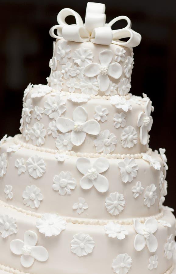 A white wedding cake. Isolated on dark royalty free stock photography
