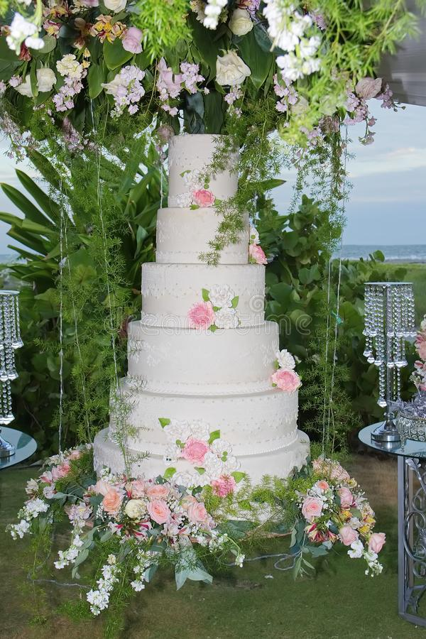 White wedding cake with flowers. Beach wedding. White wedding cake with pink and yellow flowers. Beach at background royalty free stock photography