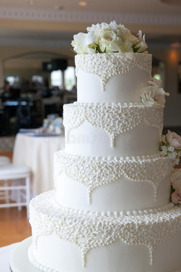 White wedding cake with white flowers and fancy designs with a reception hall in the background royalty free stock image