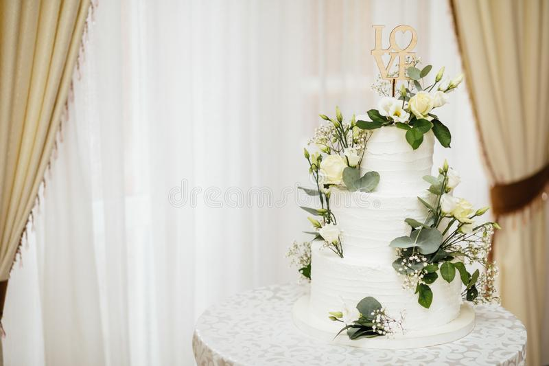 White wedding cake with flowers. The word Love with heart. royalty free stock photos