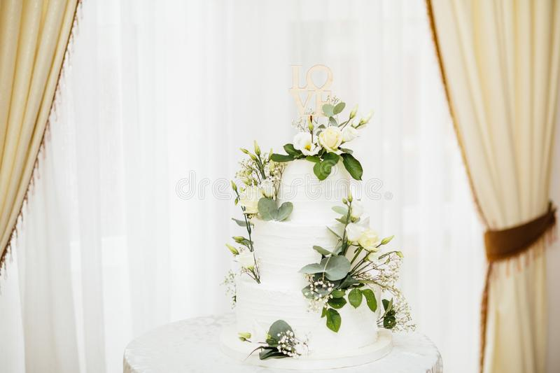 White wedding cake with flowers. The word Love with heart. stock photography