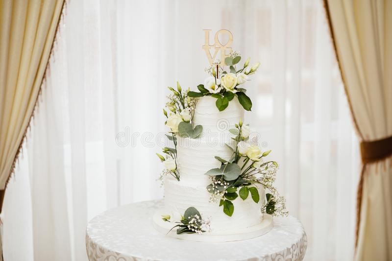White wedding cake with flowers. The word Love with heart. stock photos