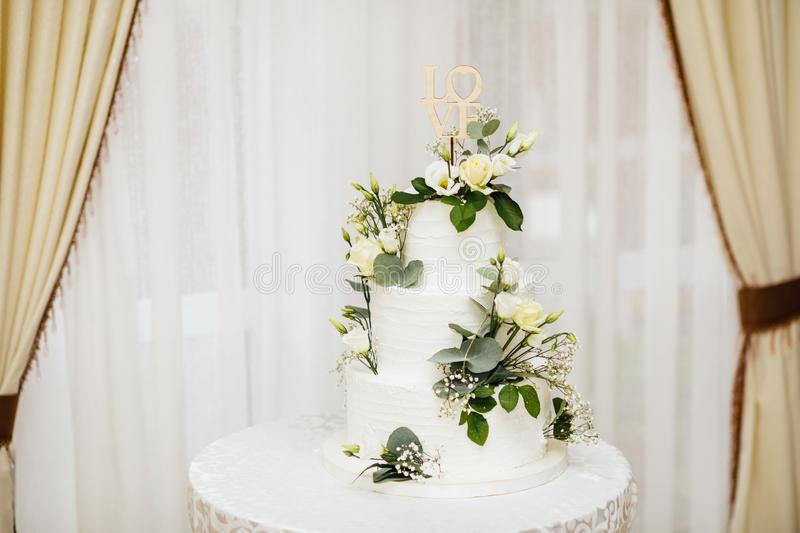 White wedding cake with flowers. The word Love with heart. royalty free stock photo