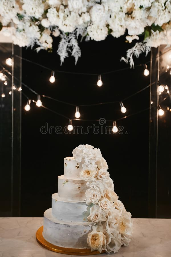 White wedding cake with peonies and roses flowers on the night ceremony outdoors. Extra large three-tiered wedding cake stock images