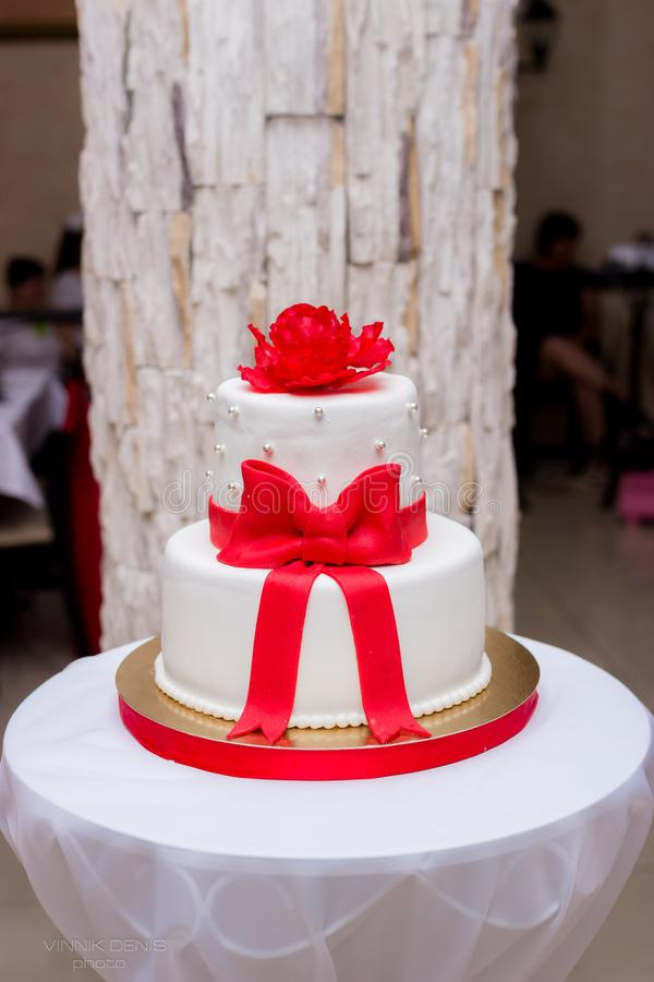 White wedding cake with red ribbons royalty free stock photos