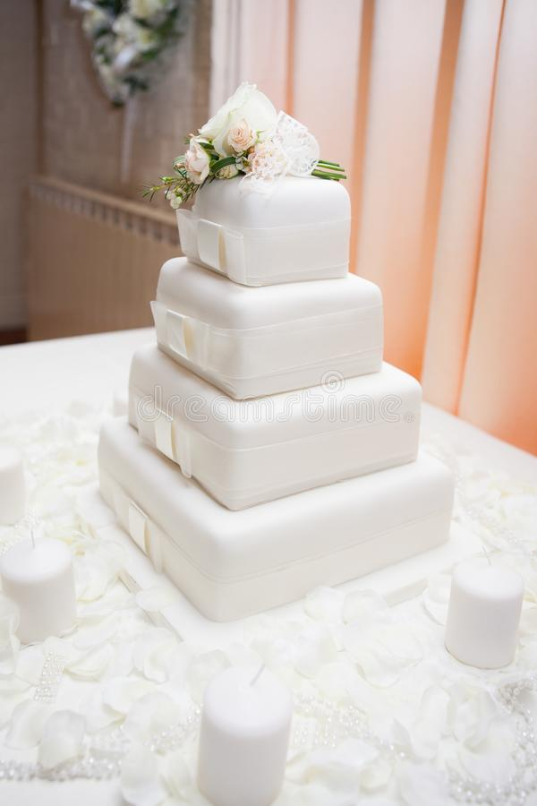 White wedding cake with flowers decorating the top and candles stock images